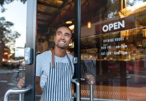 intercâmbio de trabalho: homem abrindo porta de loja