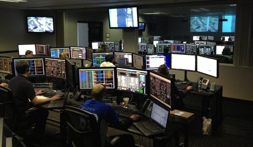 Vários monitores de computadores com profissionais de TI