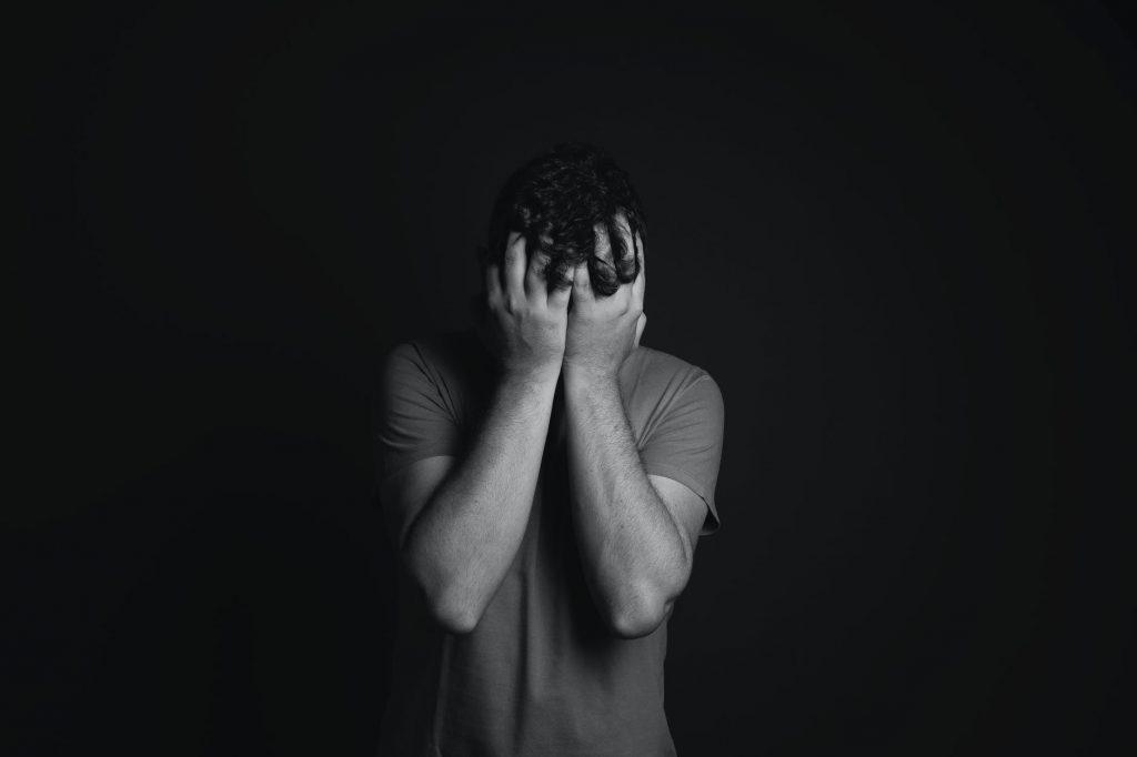 Imagem escura com uma pessoa ao centro tapando o rosto com as mãos.