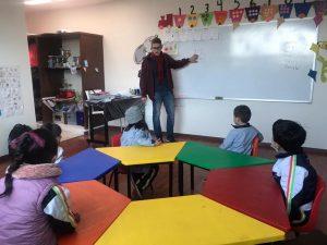 Jovem em sala de aula ministrando aula para crianças