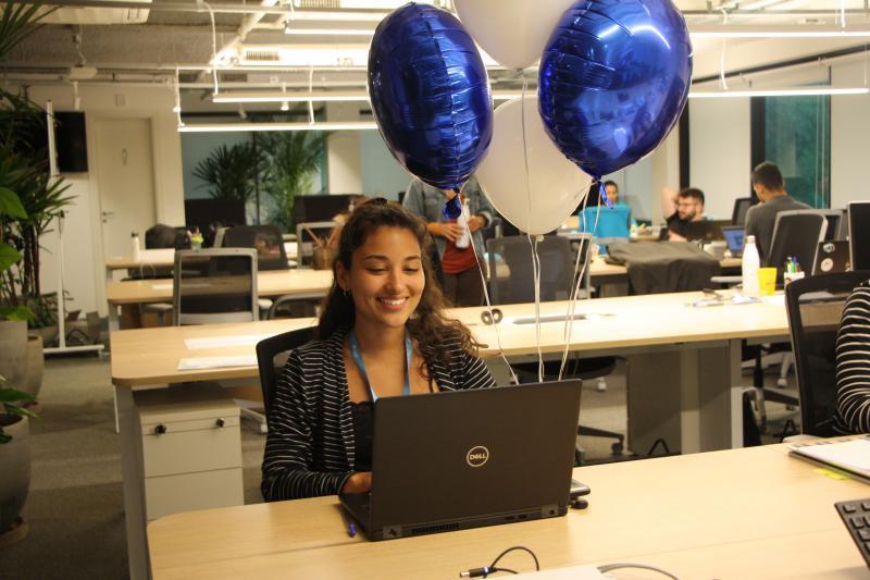 Fernanda sentada em uma mesa olhando para seu notebook e sorrindo