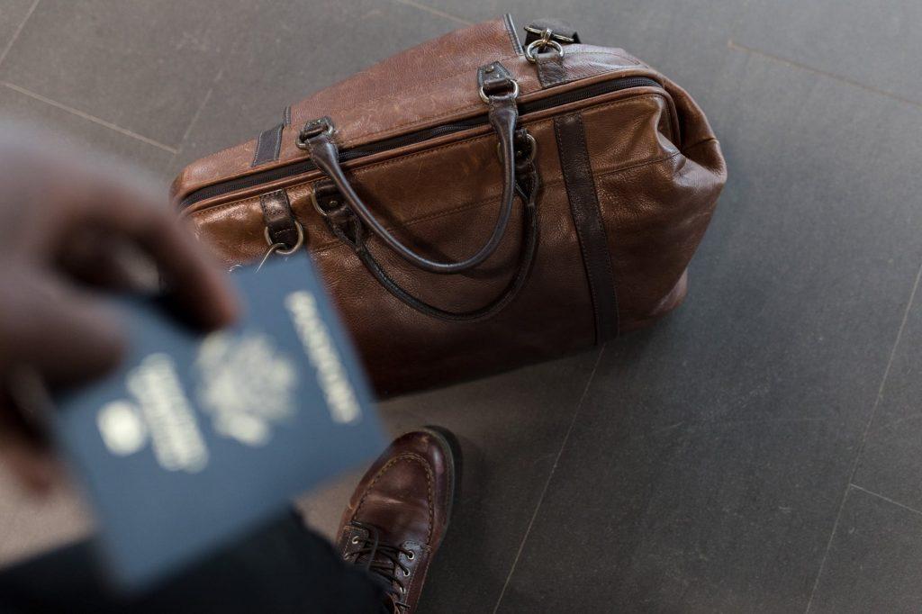 Mala ao chão com uma pessoa segurando um passaporte
