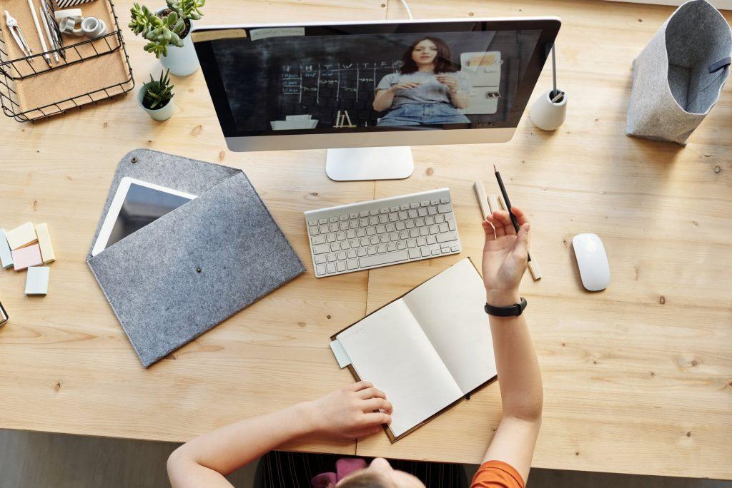 mesa com computador e alguém anotando as informações do vídeo
